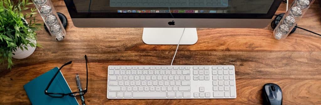 i-mac posé sur une bureau avec clavier et souris